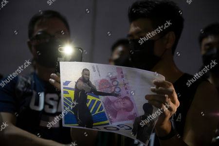 A demonstrator holds a sign showing Lebron James embracing a Chinese 100-yuan banknote during a rally at the Southorn Playground in Hong Kong, . Protesters in Hong Kong have thrown basketballs at a photo of LeBron James and chanted their anger about comments the Los Angeles Lakers star made about free speech during a rally in support of NBA commissioner Adam Silver and Houston Rockets general manager Daryl Morey, whose tweet in support of the Hong Kong protests touched off a firestorm of controversy in China