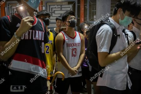 Stock Image of A demonstrator wearing a Houston Rockets jersey sings the U.S. national anthem with fellow demonstrators during a rally at the Southorn Playground in Hong Kong, . Protesters in Hong Kong have thrown basketballs at a photo of LeBron James and chanted their anger about comments the Los Angeles Lakers star made about free speech during a rally in support of NBA commissioner Adam Silver and Houston Rockets general manager Daryl Morey, whose tweet in support of the Hong Kong protests touched off a firestorm of controversy in China