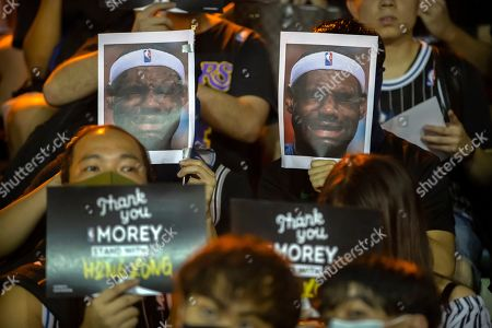 Demonstrators hold up photos of LeBron James grimacing during a rally at the Southorn Playground in Hong Kong, . Protesters in Hong Kong have thrown basketballs at a photo of LeBron James and chanted their anger about comments the Los Angeles Lakers star made about free speech during a rally in support of NBA commissioner Adam Silver and Houston Rockets general manager Daryl Morey, whose tweet in support of the Hong Kong protests touched off a firestorm of controversy in China