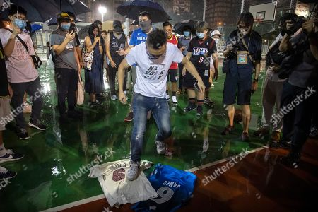 Stock Picture of A demonstrator stomps on Lebron James jerseys during a rally at the Southorn Playground in Hong Kong, . Protesters in Hong Kong have thrown basketballs at a photo of LeBron James and chanted their anger about comments the Los Angeles Lakers star made about free speech during a rally in support of NBA commissioner Adam Silver and Houston Rockets general manager Daryl Morey, whose tweet in support of the Hong Kong protests touched off a firestorm of controversy in China