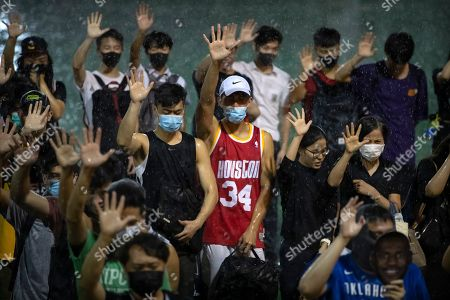 A demonstrator wearing Houston Rockets jersey holds up his hand with fellow demonstrators during a rally at the Southorn Playground in Hong Kong, . Protesters in Hong Kong have thrown basketballs at a photo of LeBron James and chanted their anger about comments the Los Angeles Lakers star made about free speech during a rally in support of NBA commissioner Adam Silver and Houston Rockets general manager Daryl Morey, whose tweet in support of the Hong Kong protests touched off a firestorm of controversy in China