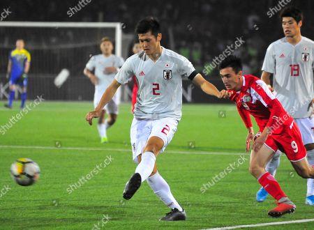 Japan's Naomichi Ueda kicks the ball ahead of Tajikistan's Karomatullo Saidov during the World Cup 2022 Qualifying Asian zone Group F soccer match between Tajikistan and Japan in Dushanbe, Tajikistan