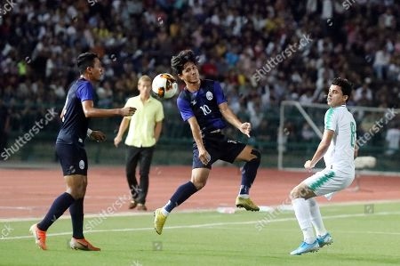 Cambodia's manager Keisuke Honda looks on as a Cambodia's soccer Kouch Sokumpheak, center, fights for the ball with Ibrahim Bayesh Al-Tameemi, of Iraq, during the World Cup second round Group C qualifying soccer match between Cambodia and Iraq in Cambodia National Stadium, in Phnom Penh, Cambodia, . Iraq won 4-0