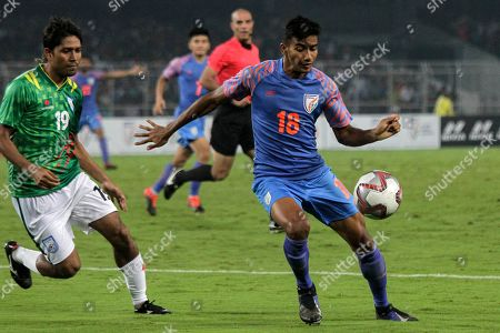 Stock Photo of India's Muhammad Asique, right vie for a ball as Bangladesh's Raihan Hasan chase him in their World Cup 2022 group E qualifying match in Kolkata, India
