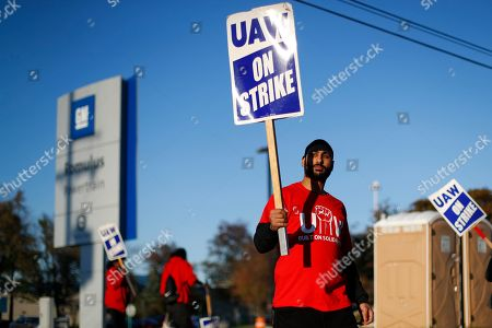 A member of the United Auto Workers walks the picket line at the General Motors Romulus Powertrain plant in Romulus, Mich. General Motors CEO Mary Barra joined negotiators at the bargaining table Tuesday, Oct. 15, an indication that a deal may be near to end a monthlong strike by members of the United Auto Workers union that has paralyzed the company's factories