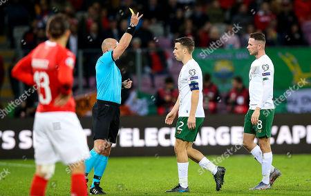 Switzerland vs Republic of Ireland. Ireland's Seamus Coleman and Granit Xhaka of Switzerland are yellow carded by referee Szymon Marciniak