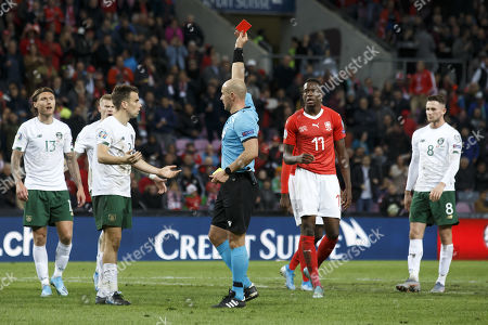 Polish referee Szymon Marciniak shows the red card to Ireland's defender Seamus Coleman, 2nd left, during the UEFA Euro 2020 qualifying Group D soccer match between Switzerland and Republic of Ireland, at the Stade de Geneve, in Geneva, Switzerland, 15 October 2019.