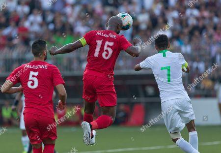 Abdallatif Albahdari, Salman Alfaraj. Palestine's Abdallatif Albahdari, center jumps for the ball in front of Saudi Arabia's Salman Alfaraj during their FIFA World Cup Asian Qualifying Group Four soccer match, at Faisal Husseini Stadium, in the West Bank city of Ramallah, . The match ended with a 0-0 draw