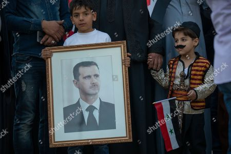 Two children hold the portrait of Syrian President Bashar al-Assad and the Syrian National flag as they are accompanying their family at a demonstration next to the Syrian Embassy in Amman, Jordan, 15 October 2019. About 200 people gathered to the Syrian Embassy in Amman to denounce the Turkish offensive against the Kurdish part of Syrian territory.
