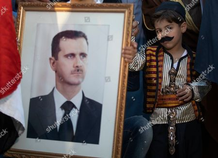 A boy dressed as an old traditional Kurdish man looks on as he stands next to the portrait of Syrian President Bashar al-Assad and the Syrian National flag as he is accompanying his family at a demonstration next to the Syrian Embassy in Amman, Jordan, 15 October 2019. About 200 people gathered to the Syrian Embassy in Amman to denounce the Turkish offensive against the Kurdish part of Syrian territory.