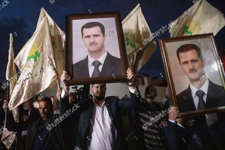 Supporters of Syrian President Bashar al-Assad hold his portrait during a demonstration next to the Syrian Embassy in Amman, Jordan, 15 October 2019. About 200 people gathered to the Syrian Embassy in Amman to denounce the Turkish offensive against the Kurdish part of Syrian territory.