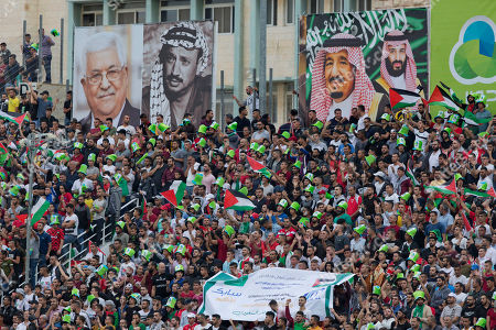 Pictures, from left, of Palestinian President Mahmoud Abbas, the late Palestinian leader Yasser Arafat, Saudi Arabia's King Salman and Crown Prince Mohammad bin Salman, adorn the stadium as fans cheer for their team during a FIFA World Cup Asian Qualifying Group Four soccer match between Palestine and Saudi Arabia, at Faisal Husseini Stadium, in the West Bank city of Ramallah, Tuesday, Oct. 15. 2019. The match ended with a 0-0 draw