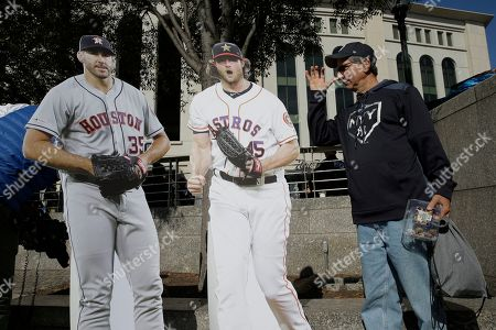 Mike Marciuliano, of New York, thumbs his nose at cutouts of Houston Astros players Houston Astros pitchers Justin Verlander (35) and Gerrit Cole (45) before Game 3 of baseball's American League Championship Series, in New York