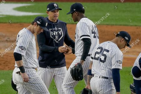 New York Yankees manager Aaron Boone, center, takes the ball and pulls starting pitcher Luis Severino (40) from the game during the fifth inning of Game 3 of baseball's American League Championship Series against the Houston Astros, in New York