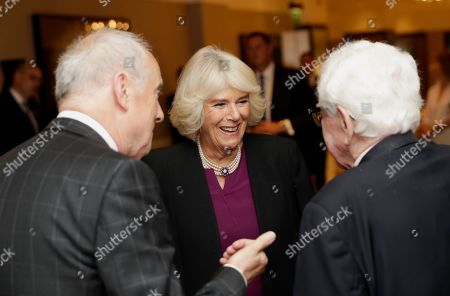 Stock Photo of Camilla Duchess of Cornwall speaks with Barry Cryer (R) as she attends a reception hosted by Gyles Brandreth (L), President of the Oscar Wilde Society, to mark the anniversary of the author's birth at the Grosvenor House