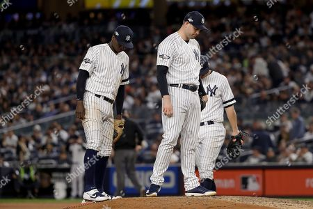 New York Yankees relief pitcher Adam Ottavino, right, and shortstop Didi Gregorius wait on the mound for manager Aaron Boone during a pitching change during Game 3 of baseball's American League Championship Series, in New York