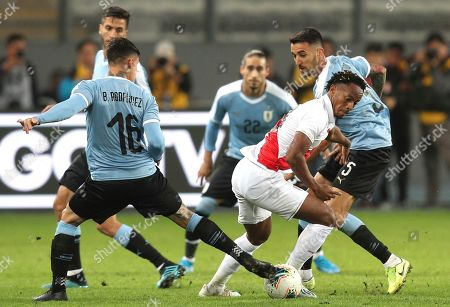Peru's Andre Carrillo, center, controls the ball between Uruguay's Brian Rodriguez, left, and Matias Vecino, behind right, during a friendly soccer match in Lima, Peru