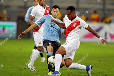 Maximiliano Gomez (C) of Uruguay in action against Renato Tapia (R) of Peru during a friendly soccer match between Uruguay and Peru at Estadio Nacional in Lima, Peru, 15 October 2019.