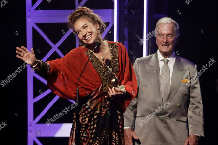 Lauren Daigle, left, accepts the song of the year award from Pat Boone, right, during the Dove Awards, in Nashville, Tenn