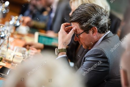 German Minister of Transport and Digital Infrastructure Andreas Scheuer sits on his place and touches his forehead during the beginning of the weekly meeting of the German Federal cabinet at the Chancellery in Berlin, Germany, 16 October 2019. During the 71st cabinet meeting, the ministers and the Chancellor are expected to discuss, among others, a draft law concerning the modification of the air traffic taxation.