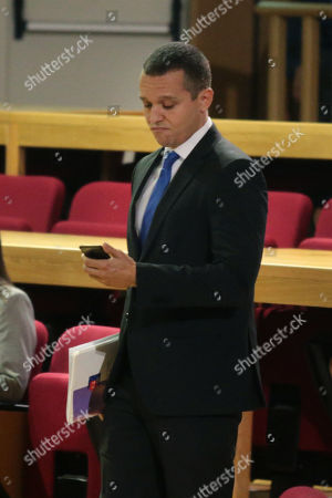 Ilias Kasidiaris, a former Member of Parliament (MP) of the extreme-right Golden Dawn party, checks his mobile phone as he comes to testify before a criminal appeals court in Athens, Greece, 16 October 2019. A total of 18 Golden Dawn officials who were elected in the Greek Parliament in 2012, are expected to testify in court as suspects. The trial began on 20 April 2015 and the extensive case file includes charges against party MPs of setting up a criminal organization.