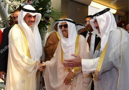 In this photo released by Kuwait News Agency, KUNA, Emir of Kuwait Sheikh Sabah al-Ahmad al-Sabah, middle, receives by Kuwaiti officials after his arrival from the U.S. in Kuwait, . Kuwait's ruling 90-year-old emir has returned to his oil-rich nation after undergoing medical checkups in the U.S. following a health scare
