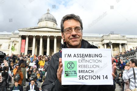Stock Photo of British journalist George Monbiot poses for photographers before being arrested by police during an Extinction Rebellion protest in London, Britain, 16 October 2019. Global climate movement Extinction Rebellion announced climate change protests and blockades worldwide for two weeks starting 07 October.