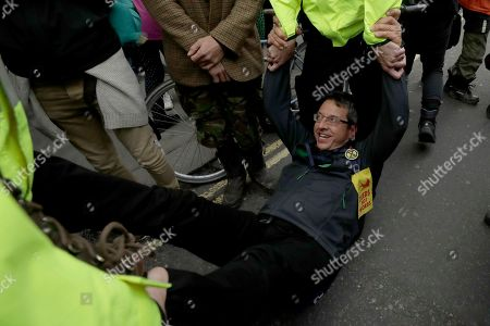 The Guardian newspaper environmental journalist and author George Monbiot is carried away by police after sitting down and blocking a road on Whitehall at the bottom of Trafalgar Square, during a rally in London, . Climate protesters in London have kept up their campaign despite being ousted by a police order from their Trafalgar Square encampment on Monday