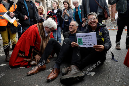 The Guardian newspaper environmental journalist and author George Monbiot, right, sits blocking a road flanked at left by the Co-Leader of Britain's Green Party Jonathan Bartley on Whitehall at the bottom of Trafalgar Square, during an Extinction Rebellion rally in London, . Climate protesters in London have kept up their campaign despite being ousted by a police order from their Trafalgar Square encampment on Monday