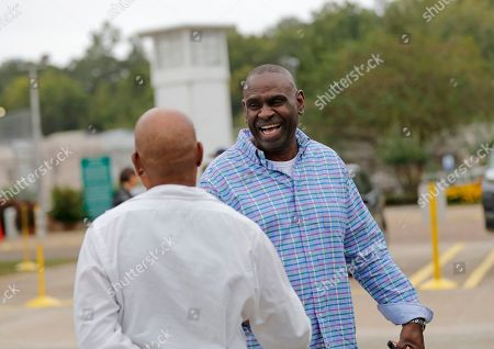 Aaron Brooks, facing, laughs with his brother Elvis Brooks, after Elvis walked out of the Louisiana State Penitentiary at Angola in Angola, La., . Brooks, who has spent two-thirds of his life in prison for a killing he always denied committing, pleaded guilty to manslaughter and was released. Innocence Project New Orleans attorneys say evidence that would have cleared him was withheld at trial. Prosecutors offered the plea agreement Tuesday which was accepted