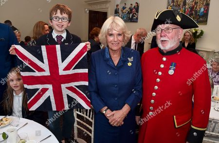 Camilla Duchess of Cornwall with Conor Kitching (L) and Chelsea pensioner Roy Palmer as she attends a reception and tea party for the 'Poetry Together' initiative, where the young and old will recite poetry at Eaton Square Upper School.