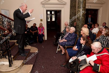 Gyles Brandreth (L) makes a speech as Camilla Duchess of Cornwall attends a reception and tea party for the 'Poetry Together' initiative, where the young and old will recite poetry at Eaton Square Upper School.
