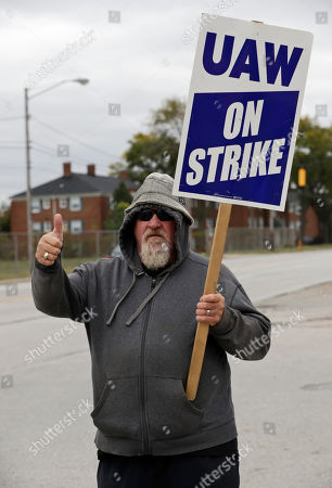 Kevin Curley, an 11-year GM employee, gives a thumbs up as he pickets outside the General Motors Fabrication Division, in Parma, Ohio. General Motors CEO Mary Barra joined negotiators at the bargaining table, an indication that a deal may be near to end a monthlong strike by the United Auto Workers union that has paralyzed the company's factories