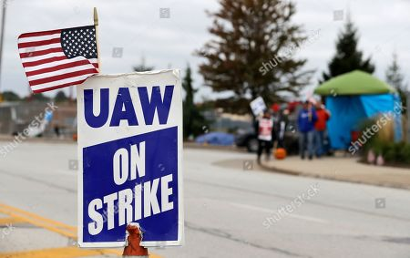 A strike sign rests on a cone in the center of the street as General Motors employees picket outside the General Motors Fabrication Division, in Parma, Ohio. General Motors CEO Mary Barra joined negotiators at the bargaining table, an indication that a deal may be near to end a monthlong strike by the United Auto Workers union that has paralyzed the company's factories