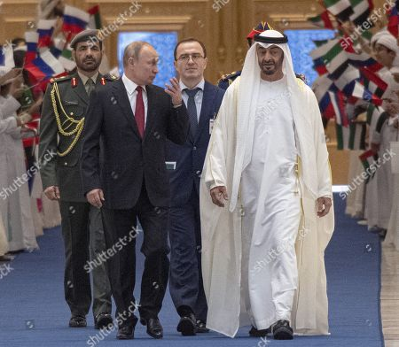 Stock Photo of Talks between Russian President Vladimir Putin and the Crown Prince of the Emirate of Abu Dhabi and Deputy Supreme Commander of the United Arab Emirates Armed Forces Crown Prince Sheikh Mohammed bin Zayed Al Nahyan took place in the Qasr Al Watan palace. Russian President Vladimir Putin, second from left, and the Crown Prince of the Emirate of Abu Dhabi and Deputy Supreme Commander of the United Arab Emirates Armed Forces Crown Prince Sheikh Mohammed bin Zayed Al Nahyan, right, during the official welcoming ceremony.