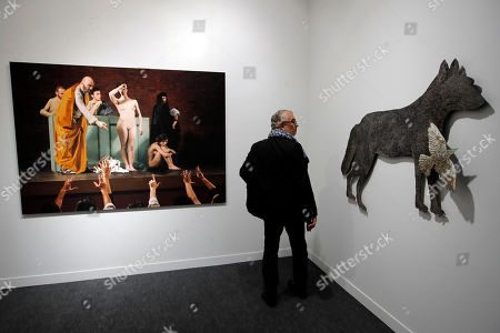 """A man stands between """"Om el Saad"""" (The Salve Market) 2019 by Egyptian artist Moataz Nasr, left, and """"Wolf and Birds IV"""", 2010 by German artist Kiki Smith, at right, displayed during the FIAC, International Contemporary Art Fair at the Grand Palais in Paris, France"""