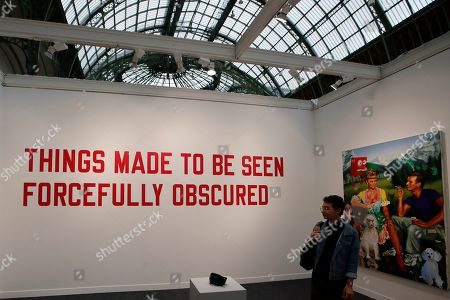 """A visitor looks at """"Things made to be seen forcefully obscured, 1996,"""" by Lawrence Weiner displayed during the FIAC, International Contemporary Art Fair at the Grand Palais in Paris, France"""