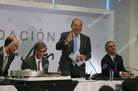 Mexican billionaire Carlos Slim, standing, jokes with journalists at the end of a news conference in Mexico City,. Slim says he supports President Andrés Manuel López Obrador's objectives