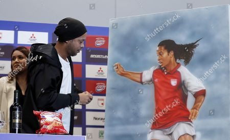 Stock Photo of Former Brazilian soccer player Ronaldinho prepares to autograph a drawing that represents him wearing the Santa Fe shirt during a press conference, in Bogota, Colombia, 16 October 2019. Ronaldinho arrived in Colombia to play two exhibition matches in Bogota and Cali. The first one will be played at the Nemesio Camacho El Campin stadium, where the Brazilian star will wear the shirt of Independiente Santa Fe in the game against Atletico Nacional. The second match will be in Cali, in the classic between America and Deportivo Cali, at the Pacual Guerrero stadium, where Gaucho will play one half with each team.