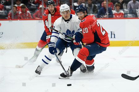 Stock Photo of Washington Capitals center Lars Eller (20), of Denmark, vies for the puck against Toronto Maple Leafs center Trevor Moore (42) during the first period of an NHL hockey game, in Washington
