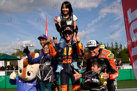 (R-L) Spanish MotoGP rider Aleix Espargaro of Aprilia Racing Team Gresini, Spanish MotoGP rider Pol Espargaro of Red Bull KTM Factory Racing and Malaysian MotoGP rider Hafizh Syahrin of Red Bull KTM Tech 3 Team pose with children at a fan event at Twin Ring Motegi in Motegi, Japan, 17 October 2019. The event was held ahead of the MotoGP race of Japan's Motorcycling Grand Prix scheduled for 20 October 2019.