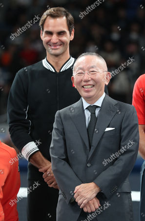 Japan's apparel giant Uniqlo president Tadashi Yanai (R) smiles with Uniqlo ambassador Swiss tennis player Rodger Fedeler as Uniqlo holds a charity tennis event