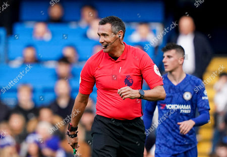 Referee Andre Marriner laughs after falling over backwards on the pitch
