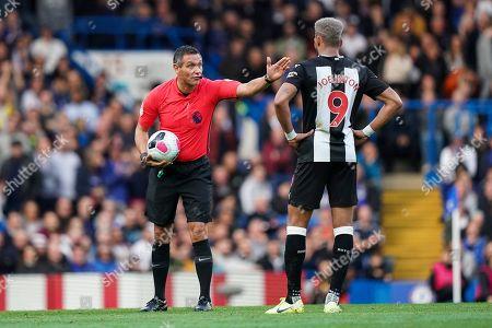 Referee Andre Marriner talks to Joelinton of Newcastle United