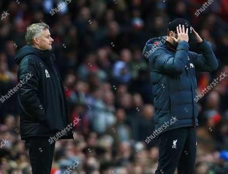 Liverpool manager Jurgen Klopp holds his head next to counterpart Ole Gunnar Solskjaer of Manchester United