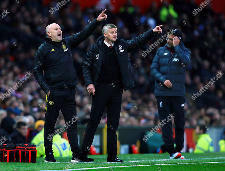 Manchester United manager Ole Gunnar Solskjaer and assistant Mike Phelan issue instructions next to a dejected looking Jurgen Klopp of Liverpool
