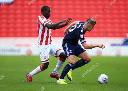 Tom Cairney of Fulham and Badou Ndiaye of Stoke City
