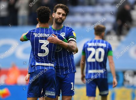 Stock Picture of Antonee Robinson and Charlie Mulgrew of Wigan Athletic congratulate each other at full time