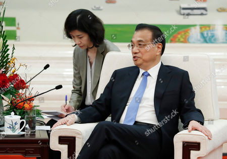 Chinese Premier Li Keqiang speaks with Chairman of the U.S.-China Business Council Evan Greenberg, at the Great Hall of the People in Beijing