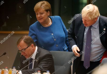 British Prime Minister Boris Johnson, right, and German Chancellor Angela Merkel, center, look over the shoulder of Swedish Prime Minister Stefan Lofven during a round table meeting at an EU summit in Brussels,. Britain and the European Union reached a new tentative Brexit deal on Thursday, hoping to finally escape the acrimony, divisions and frustration of their three-year divorce battle